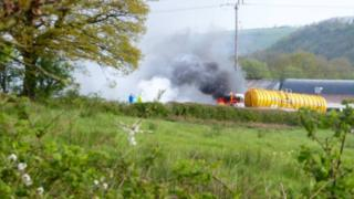 A photo of a fuel tanker on fire - thick smoke billows into the air. The surrounding area is very rural looking