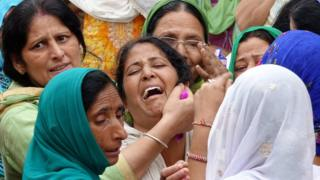 Indian relatives of bus accident victims cry as the bodies (not pictured) are carried to a funeral