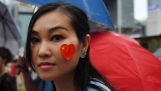 香港添馬公園親政府集會上一名女示威者在臉頰貼上中國國旗(17/8/2019)