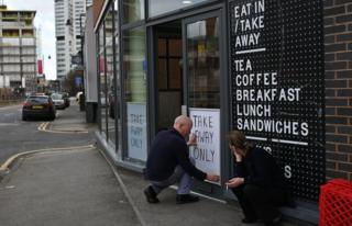 """A sign saying """"Take Away Only"""" is attached to the window of a cafe in Leeds, northern England on March 21, 2020, a day after the British government said it would help cover the wages of people hit by the coronavirus outbreak as it tightened restrictions to curb the spread of the disease."""