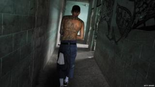 A member of the the 18th street gang walks down a hallway in the Quezaltepeque prison in 2012