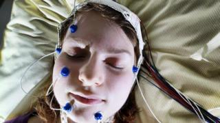 Mujer durmiendo con electrodos