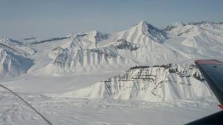 Montañas nevadas vistas desde la ventanilla de un avión.