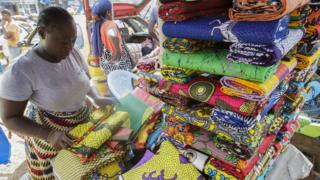 in_pictures A market woman folding cloth at her stall in Monrovia, Liberia - Tuesday 19 November 2019