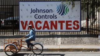 Un carretillero pasa por un cartel de una empresa que busca empleados