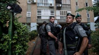 Israeli police stand outside a block of flats in Kiryat Gat where a Palestinian was shot after stabbing an Israeli soldier and stealing his rifle (7 October 2015)