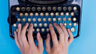 "Hands typing on a manual ""qwerty"" typewriter"