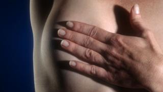 Mujer con la mano en el seno.