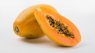A photo of the maradol papaya - a large oval fruit with an orange colour. One fruit is cut in half, showing the dark seeds clustered in its core