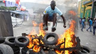 A protester jumps over a burning barricade during a protest against the government in the streets of Port-au-Prince
