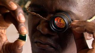 Woora Make lab founder Gnikou Afate examines a microchip using this rudimentary magnifier