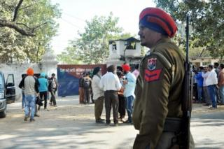 Police and onlookers stand near the gate of the Nabha maximum-security jail in Nabha in the state of Punjab on 27 November