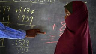 A young pupil stands next to her teacher as he points at mathematical sums on a blackboard
