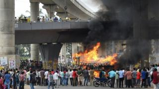 "Onlookers watch as a truck from neighbouring state Tamil Nadu burns after it was set alight by agitated pro-Karnataka activists as the Cauvery water dispute erupted following the Supreme Court""s order to release water to Tamil Nadu, in Bangalore on September 12, 2016."