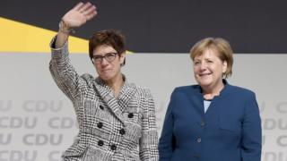 The elected chairwoman Annegret Kramp-Karrenbauer (L) waves next to German Chancellor Angela Merkel