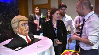a woman shows a cake at election night trump HQ