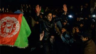 """Afghan cricket fans celebrate their team""""s victory in the match between Afghanistan and Zimbabwe as they watch it on a big screen at a stadium in Jalalabad on January 6, 2016."""