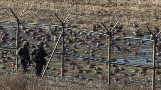 South Korean soldiers patrol a fence near the DMZ
