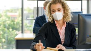 Woman wearing mask working in an office