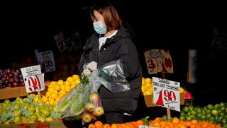 A woman wears a mask and gloves as he shops at a fruit stand in New York