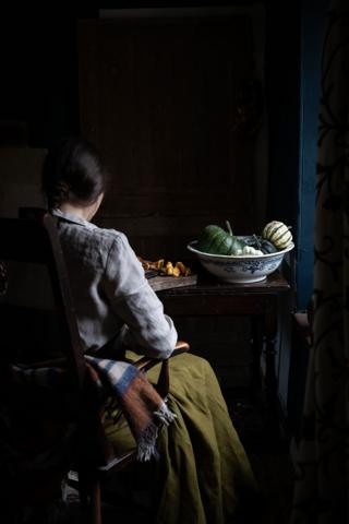 A woman sits at a table with a bowl of squash in front of her