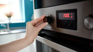 Close up of woman's hand setting temperature control on oven.