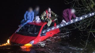 Fireman rescues teenagers from top of stranded car