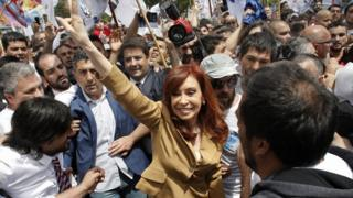 Cristina Fernandez de Kirchner waves at a large crowd of supporters while protected by a human barrier outside the court.