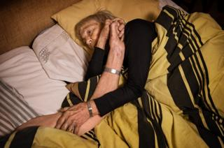 An elderly couple lie in bed holding hands.