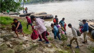 Migrants cross the Suchiate River, which delimits the border between Guatemala and Mexico, in the state of Chiapas, Mexico, on 11 June 2019. T