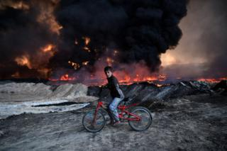 A boy pauses on his bicycle as he passes an oil field that was set on fire by retreating ISIS fighters ahead of the Mosul offensive, on 21 October 2016 in Qayyarah, Iraq.