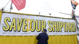 Man signing 'Saved our Shipyard' poster at Harland and Wolff