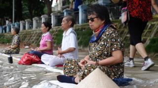 Một nhóm người dân khác tập luyện Pháp Luân Công bên bờ hồ ở Hà Nội