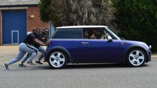 Bobsleigh team members pushing car