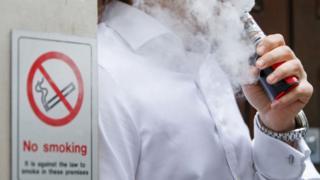 A man vaping next to a no smoking sign