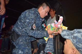 Un miembro de Protección Civil de Chiapas con un bebé entre las manos en Tapachula, en el sur de México.