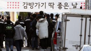 22일 이 전 대통령의 서울 논현동 사저 근처에서 시민들이 현수막을 들고 있다