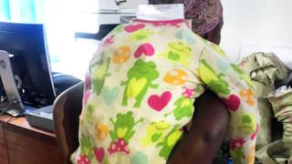 A smuggler pictured with the baby grow full of banned costmetics
