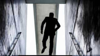 Silhouette of a man at the top of a flight of stairs