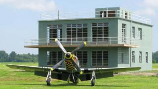 Green building with a WWII aircraft stationed in front