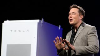 Elon Musk, right of frame, stands near a large rectangular Tesla-branded white power storage unit on stage during a 2015 press event
