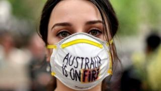A woman wearing a mask saying Australia is on Fire at a climate protest