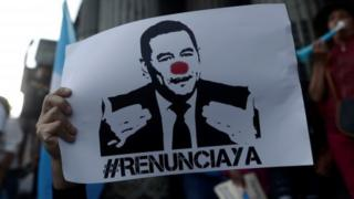 A protester holds up a sign calling for the resignation of Guatemalan President Jimmy Morales