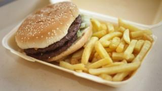 A burger and chips in a takeaway box