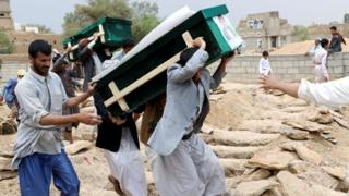 Mourners carry coffins during a funeral of people, mainly children, killed in a Saudi-led coalition air strike on a bus in northern Yemen, in Saada, Yemen on 13 August 2018.