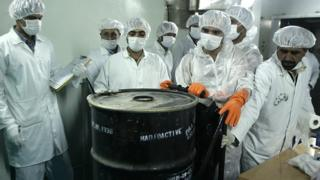 """Iranian technicians remove a container of radioactive uranium, """"yellow cake"""", sealed by the International Atomic Energy Agency, to be used at the Isfahan plant. Photo: August 2005"""