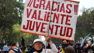 Hombre de edad sostiene letrero en protestas en chile