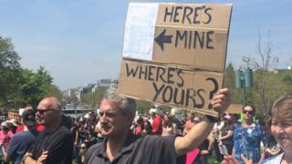 一名示威者公开展示他的税务纪录,并举着一个牌子,问特朗普的纪录在哪。
