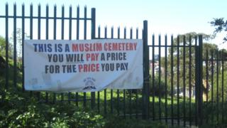 A protest sign outside a cemetery