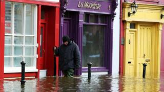 A man walks past flooded shop fronts in Bandon, Co Cork, following Storm Frank